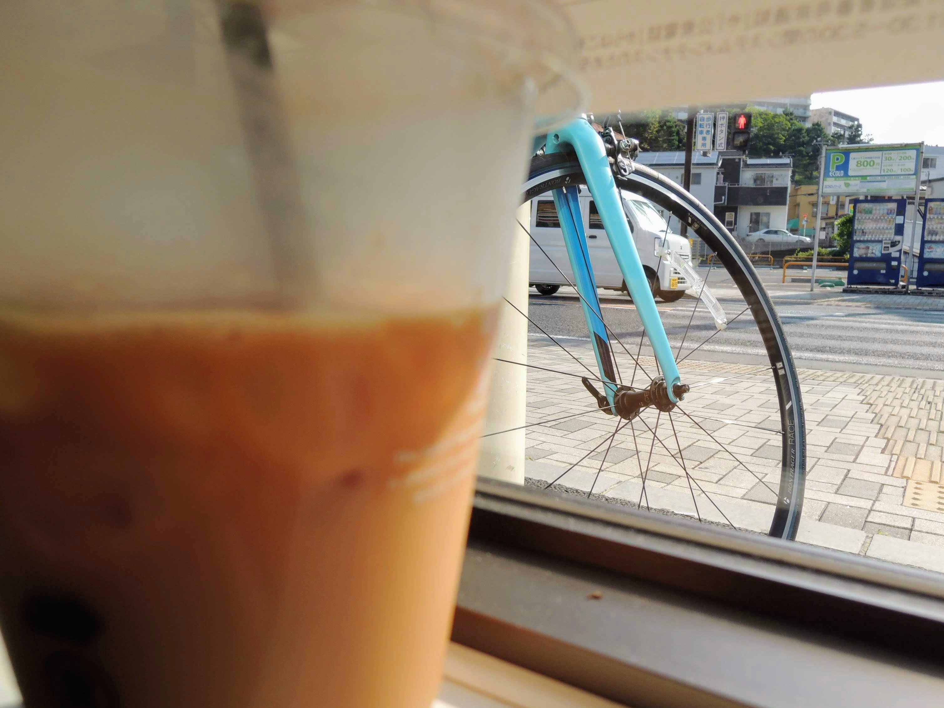 ショップ集合前にコンビニで補給。盗撮のようなアングルで自分のロードバイクをチラシ見しながらアイスコーヒー♪