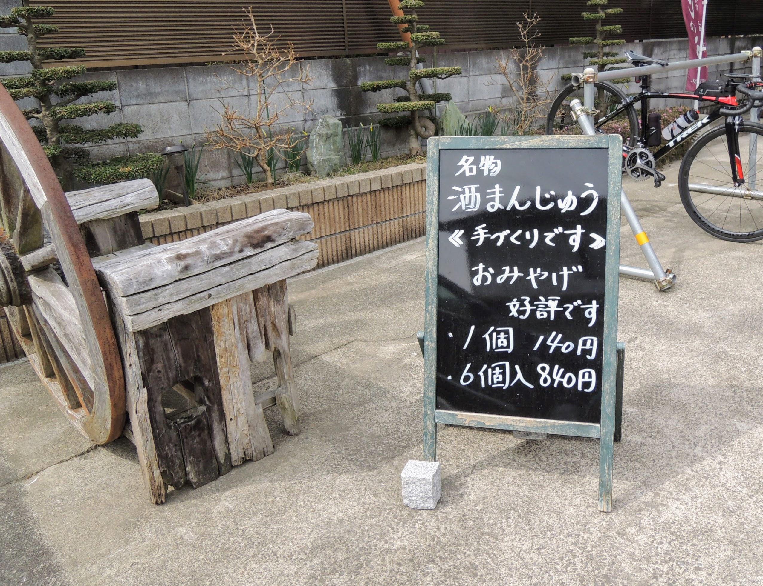 サイクルラックと酒まんじゅうの看板